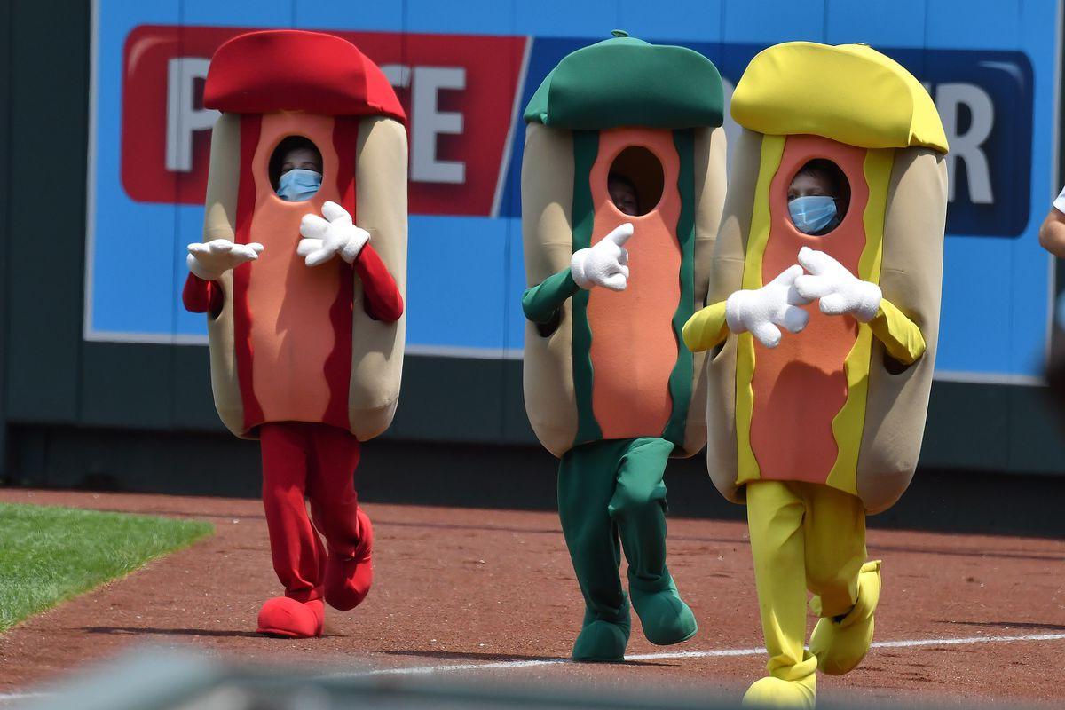 Three people in foam hot dog costumes racing in a baseball stadium