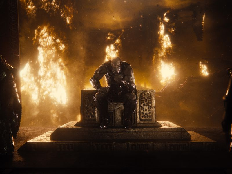 A muscled superhero sits on a throne with flames around him.