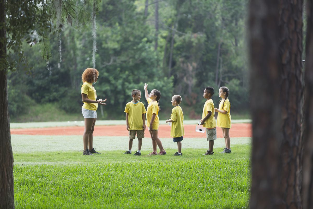 A camp counselor stands in a field in front of children in yellow shirts, as one raises their hand.