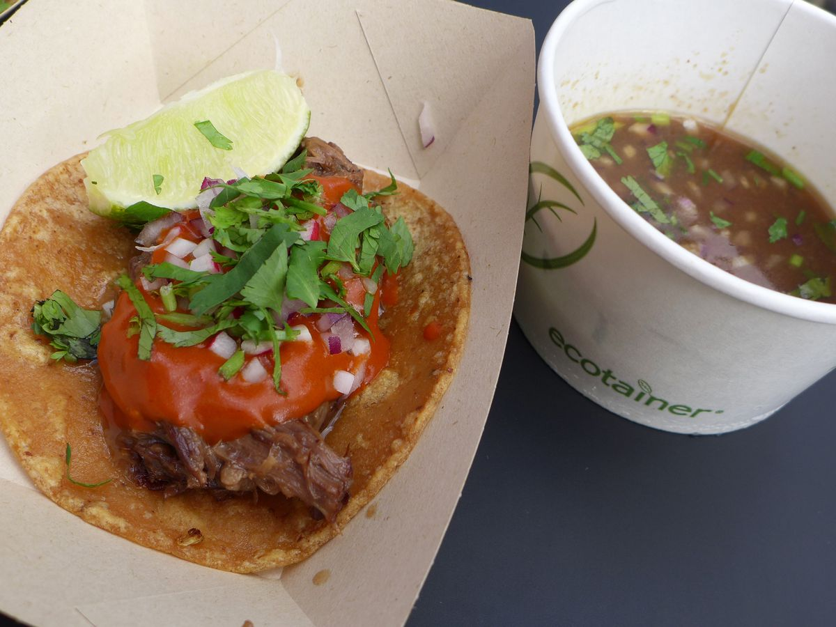 A small taco with a wad of meat and thick pink sauce alongside a cub of brown soup.