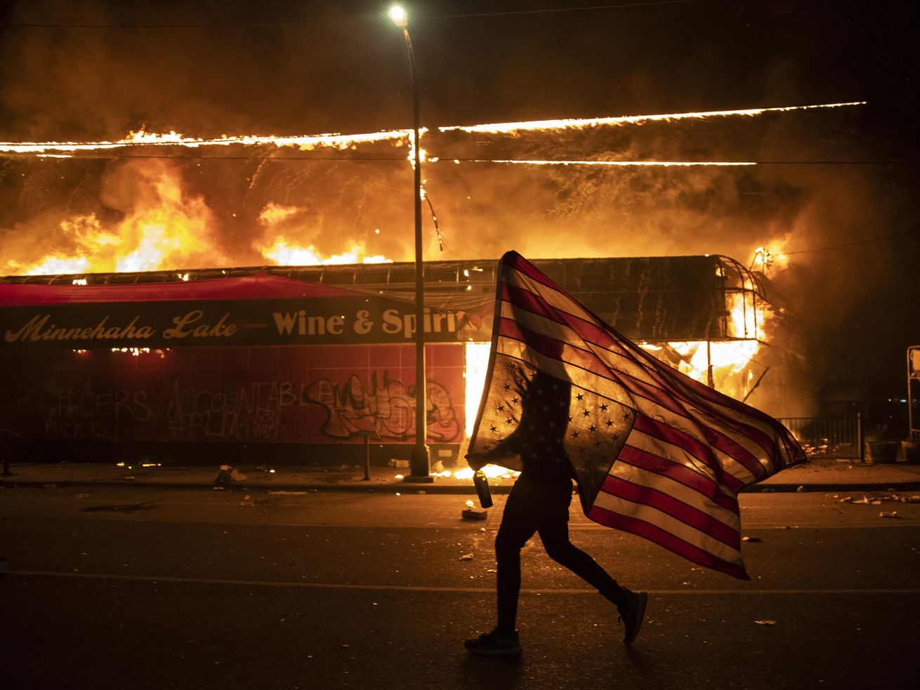 A protester carries a U.S. flag upside down, a sign of distress, next to a burning building, May 28, 2020, in Minneapolis. Protests over the death of George Floyd, a black man who died in police custody, broke out in Minneapolis for a third straight night. The image was part of a series of photographs by The Associated Press that won the 2021 Pulitzer Prize for breaking news photography.