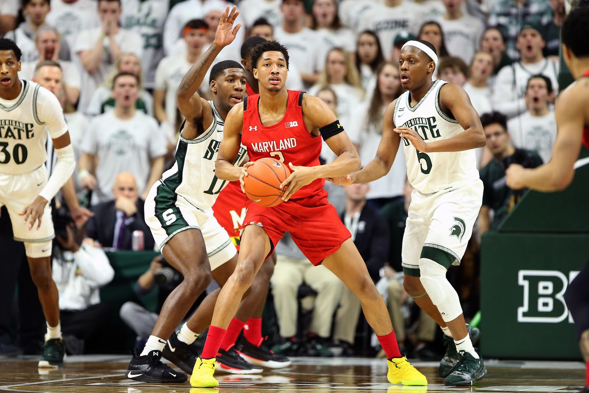 Maryland Terrapins guard Aaron Wiggins controls the ball against Michigan State Spartans forward Aaron Henry and guard Cassius Winston during the second half at the Breslin Center.