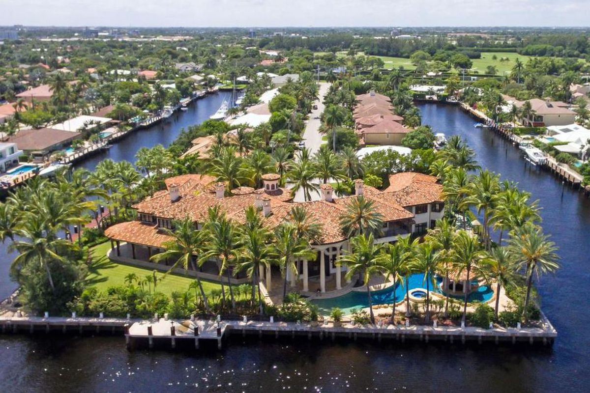 Aerial view of a huge mansion on the water in Fort Lauderdale on a point lot with a huge pool in the backyard, plenty of palm trees, and an orange roof