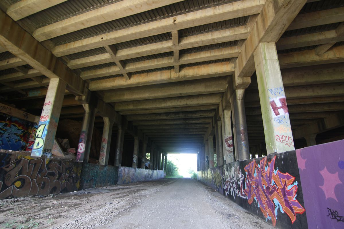 The underside of a highway with graffiti on the pillars and concrete.