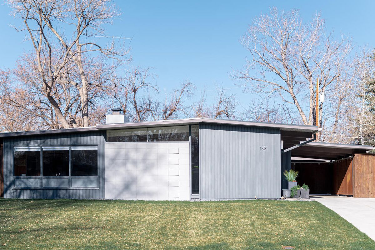 An exterior view of a gray and white midcentury modern home with a carport on the right and green grass in the front.