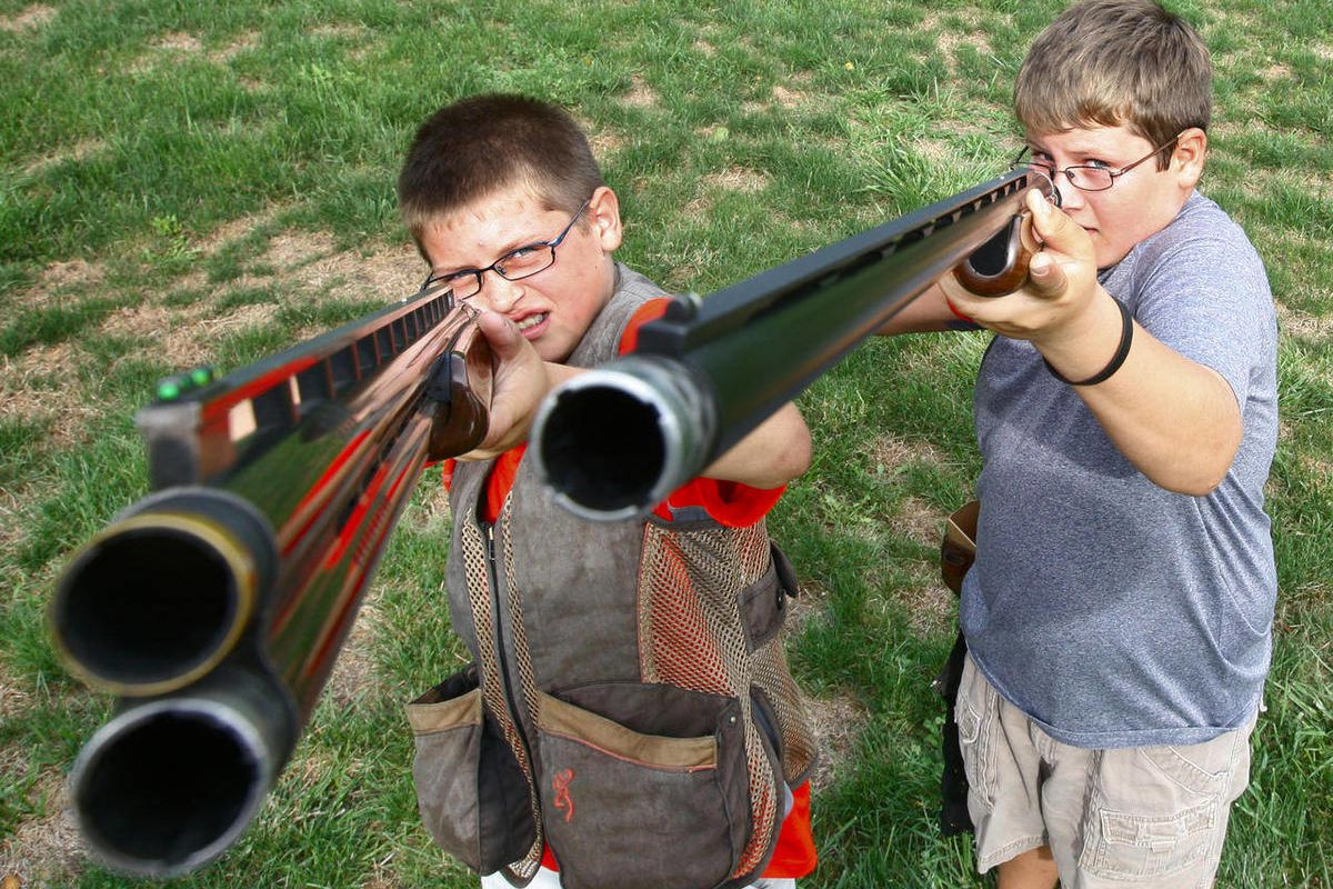 In this Sept. 14, 2012 photo, trapshooting brothers Gage Thornton, 9, left, and Hunter Thornton, 11, show off their award-winning aim in rural Bethalto, Ill., after being recognized in a trapshooting competition. Gage recently set what could be a world re