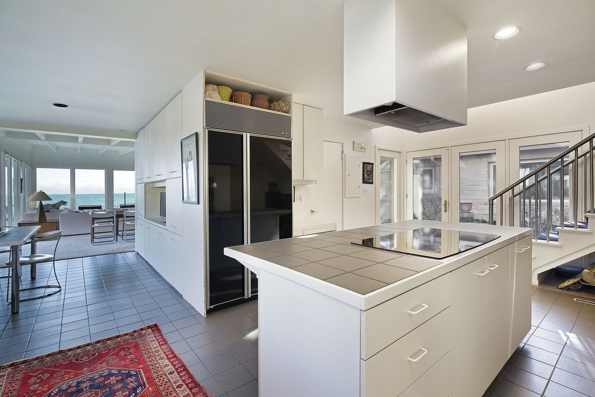 A white modern kitchen with a tile countertop and flat-top cooking range on the island.