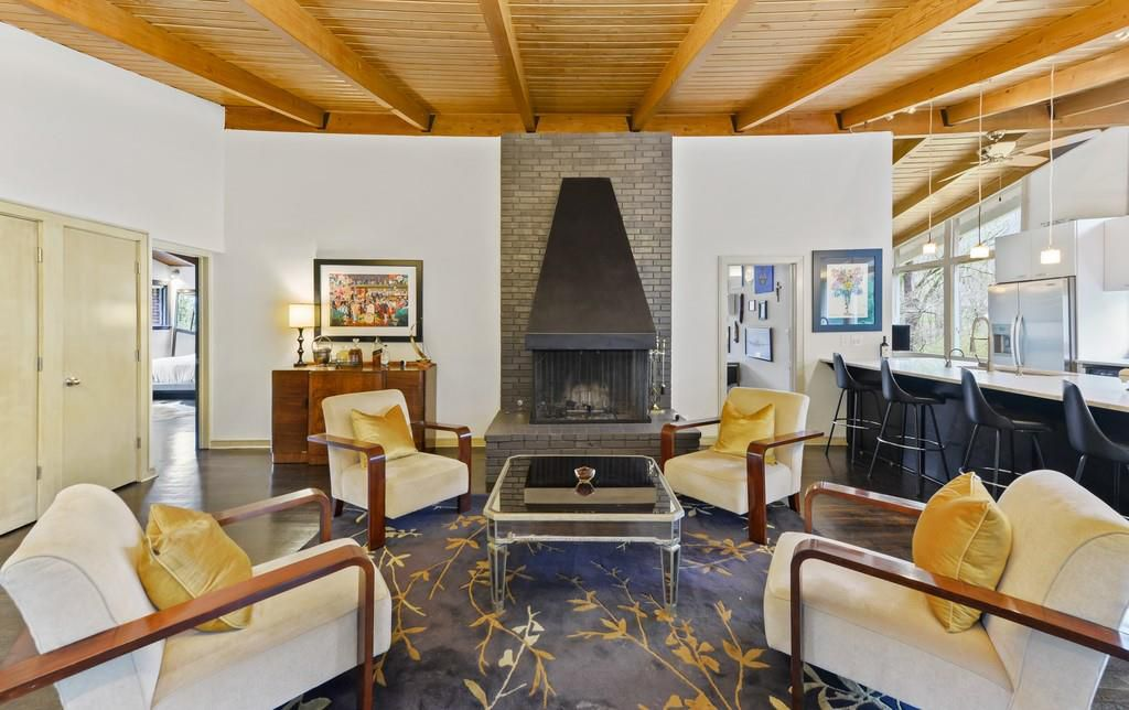 A sitting area with yellow chairs and a kitchen at right and large fireplace.