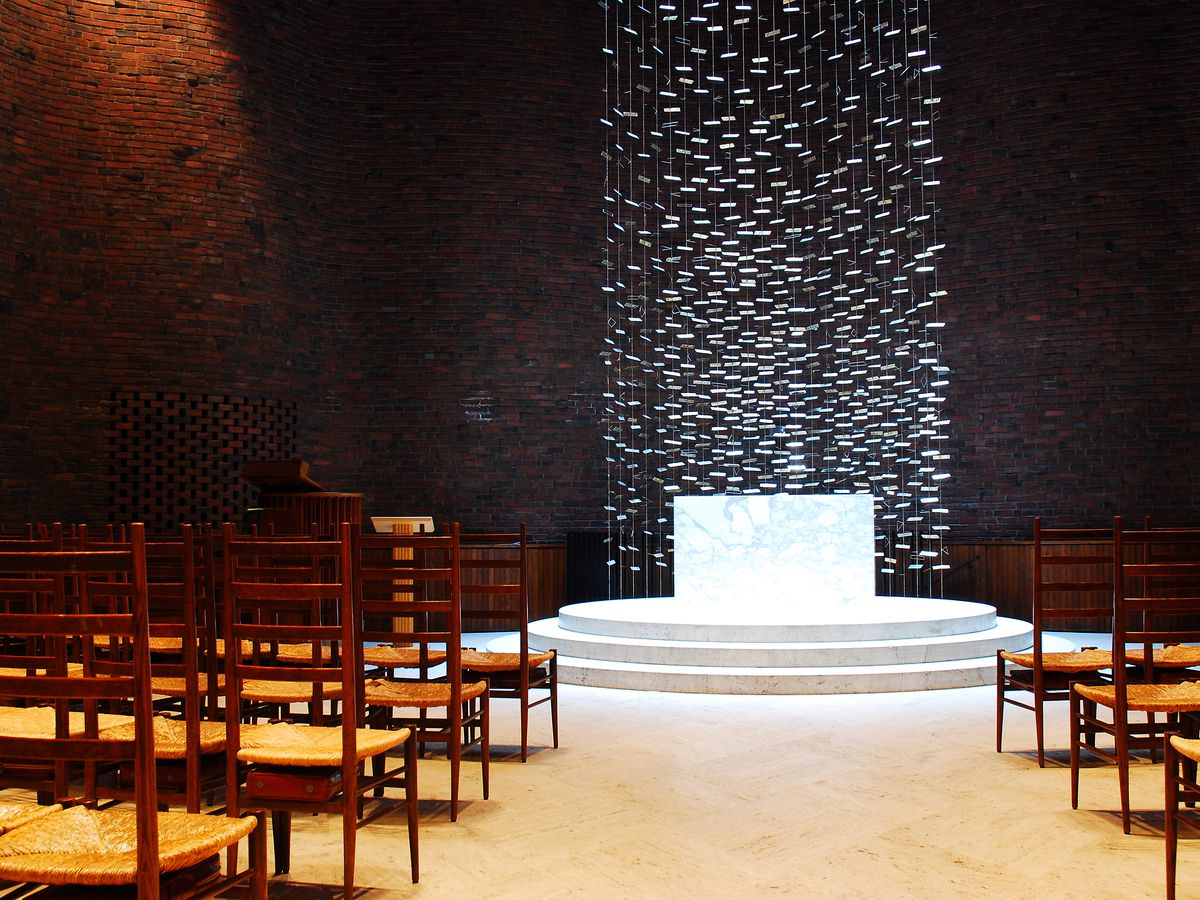 The interior of the MIT chapel. There are rows of chairs and a stage. The walls are red brick.