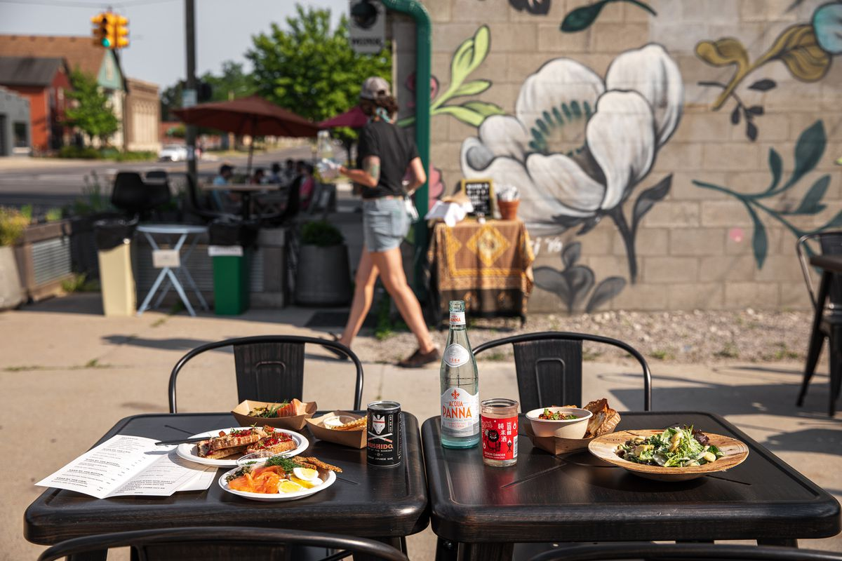 A staff member walks by a patio table filled with food.