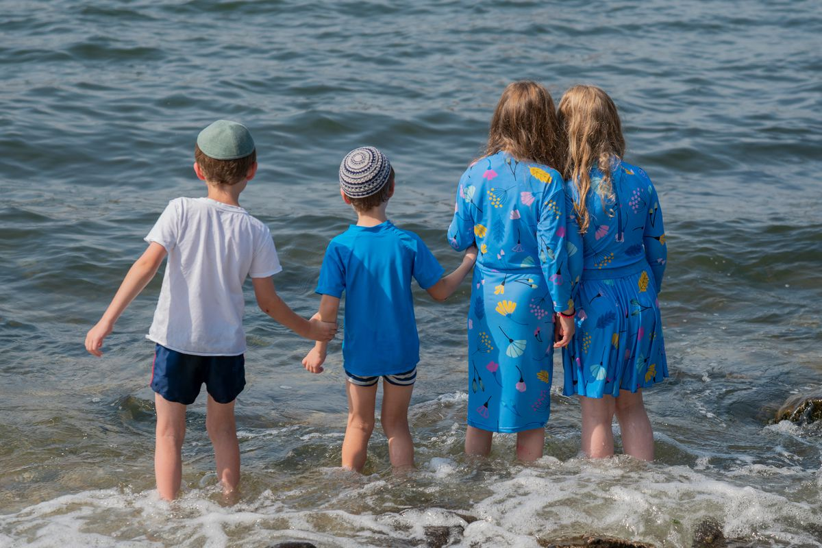 A group of kids keep each other safe at Brooklyn's Pebble Beach, Aug. 28, 2020.