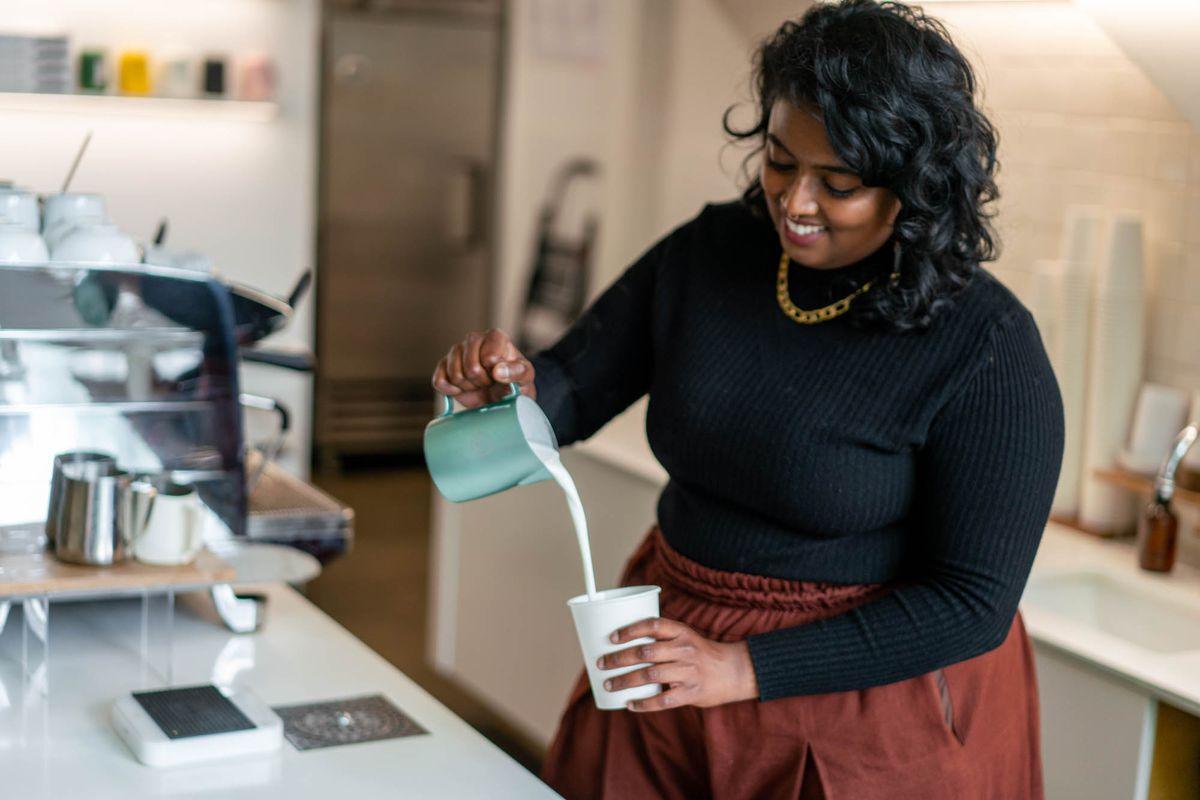 Union Coffee owner Geetu Vailoor in a long-sleeved black shirt and a tan skirt, smiling as she pours a latte into a paper cup