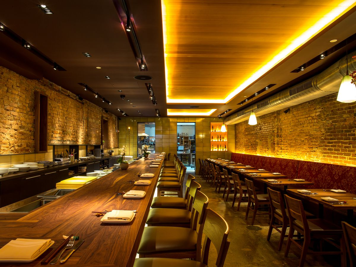 O Ya's dining room with long wooden tables and exposed brick walls