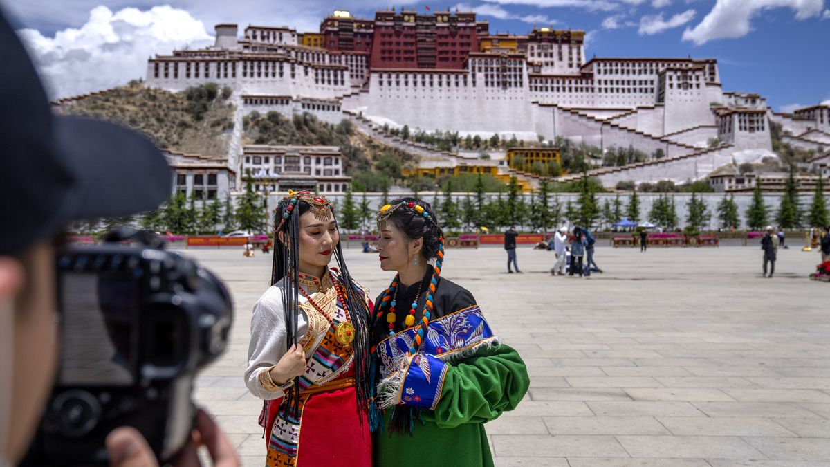 Chinese tourists in Tibetan dress pose for a photo at a square near the Potala Palace in Lhasa in western China's Tibet Autonomous Region.