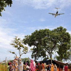 FILE - In this photo taken Friday, Sept. 14, 2012, a World Food Programme (WFP) airplane flies over a line of women and children waiting for a health screening, in Yida camp, South Sudan. Newly arrived refugees at the camp along the volatile South Sudan-Sudan border say renewed fighting between rebels and Sudan's military is likely to send thousands more people to the expanding camp there filled with refugees of war and hunger.