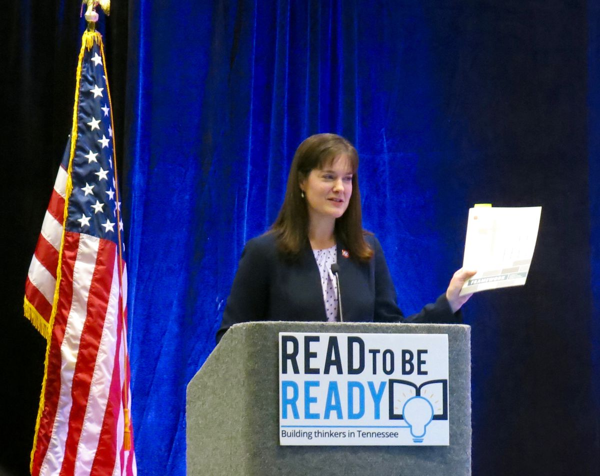 McQueen holds up a report detailing the second year of Tennessee's Read to be Ready initiative.