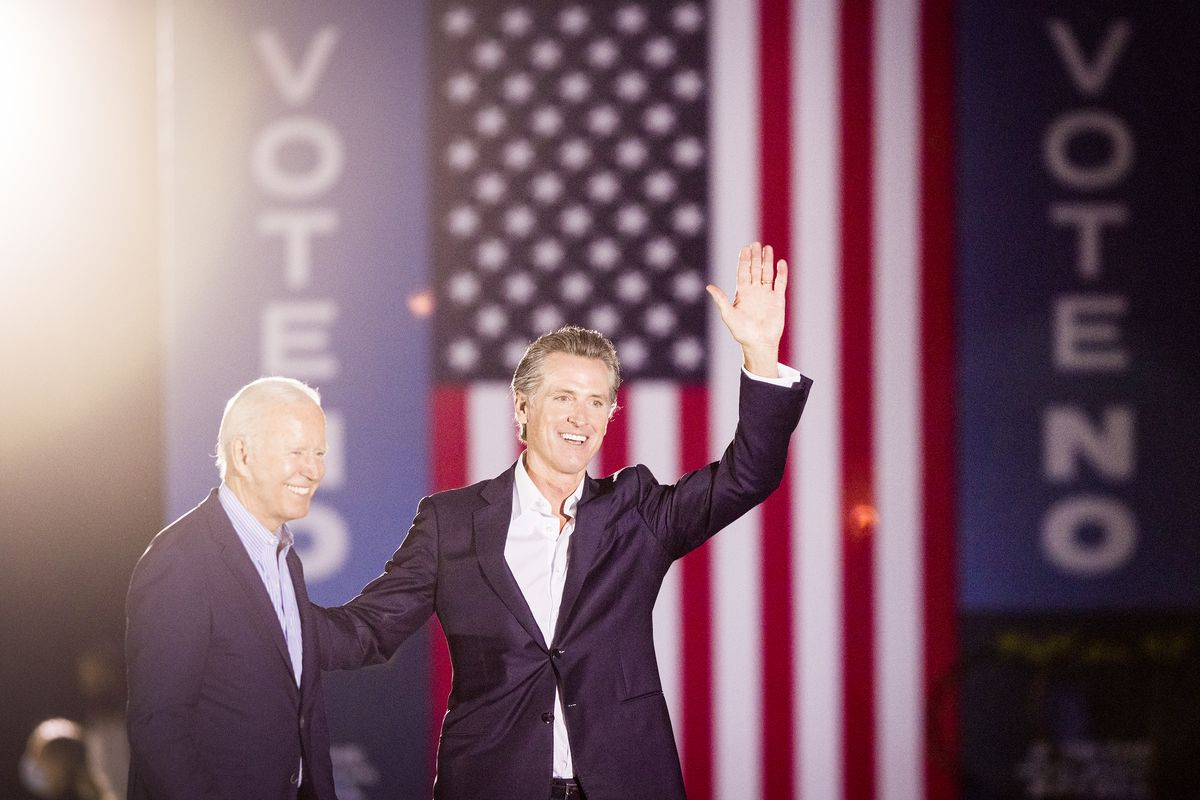"""California governor Gavin Newsom waves from onstage with President Joe Biden in front of an American flag backdrop and signs that read, """"Vote no."""""""