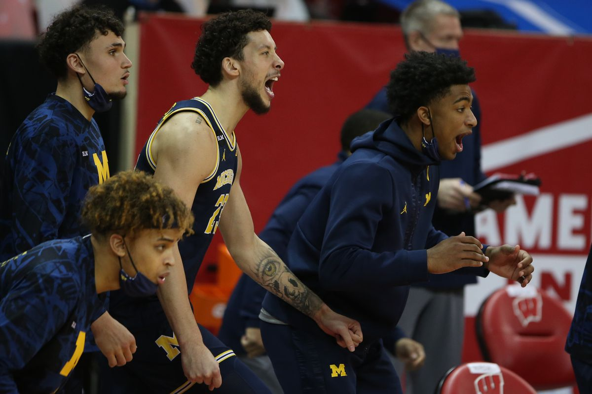 The Michigan Wolverines bench cheers after a play in the game with the Wisconsin Badgers during the second half at the Kohl Center.