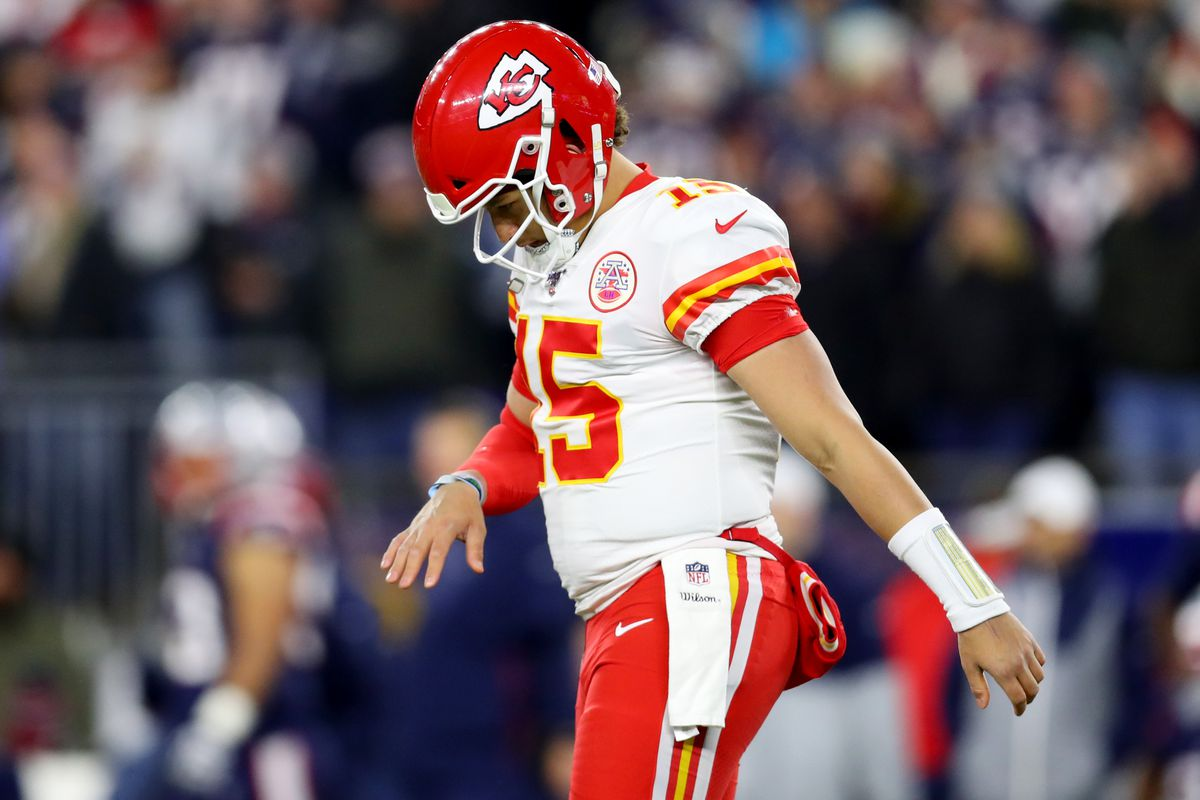 Patrick Mahomes of the Kansas City Chiefs looks down at his hand during the first half of the game against the New England Patriots at Gillette Stadium on December 08, 2019 in Foxborough, Massachusetts.