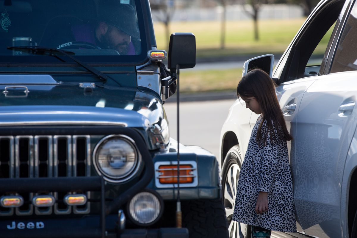 Lily Werner, 8, prays withthe Rev.Stephen Tilley, of St. John the Baptist Parish, as he sits in his Jeep for drive-up confessions at a roundabout outside the Skaggs Catholic Center in Draper on Sunday, March 22, 2020.