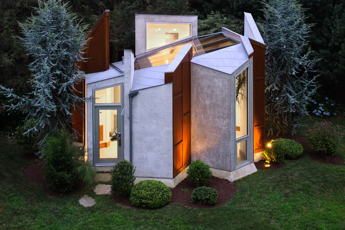 Multi-faceted standalone studio with asymmetrical panels surrounded by trees.