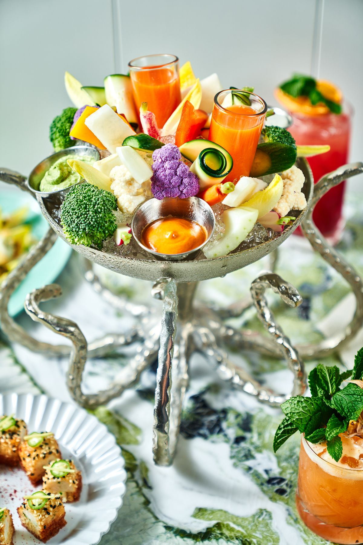An ornate silver platter with a selection of vegetable crudite.