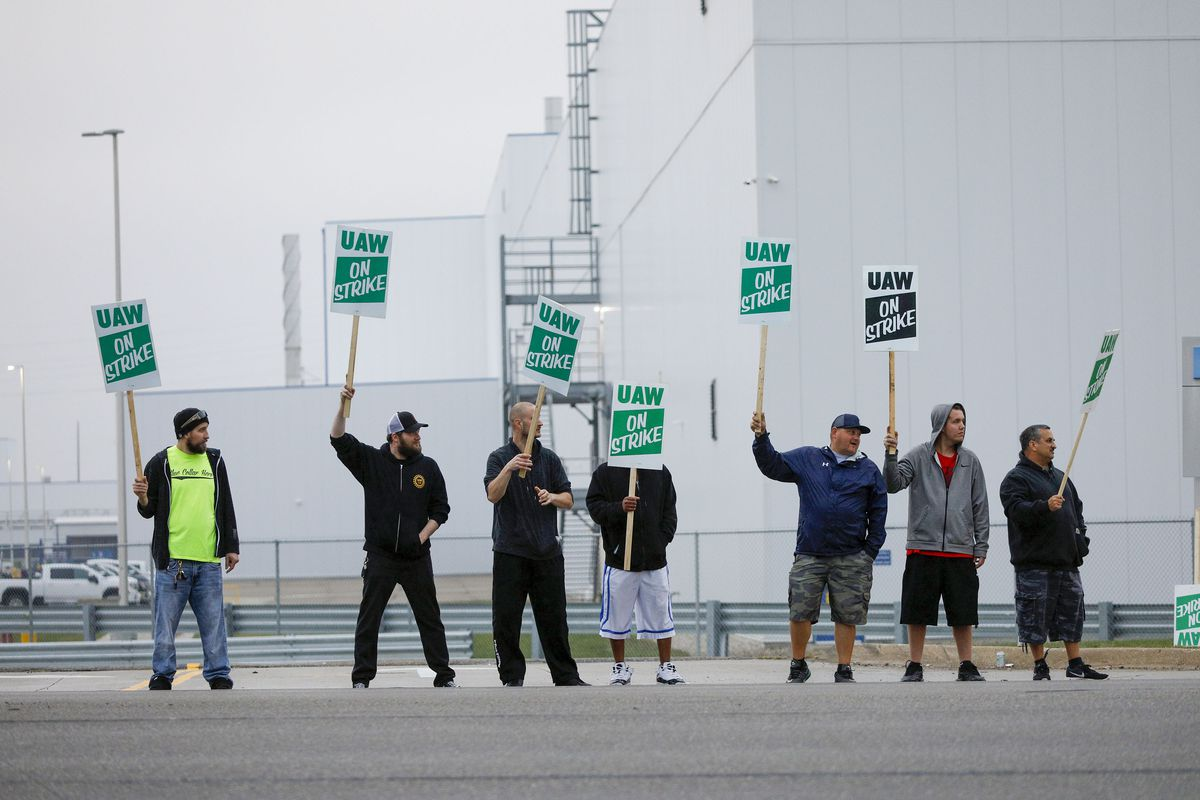 "Seven men stand outside a General Motors factory waving picket signs that read ""UAW on Strike."""