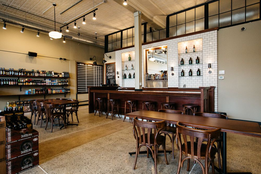 The bar at 8 Degrees Plato features dark wood and a white subway tiled back bar displaying growlers.