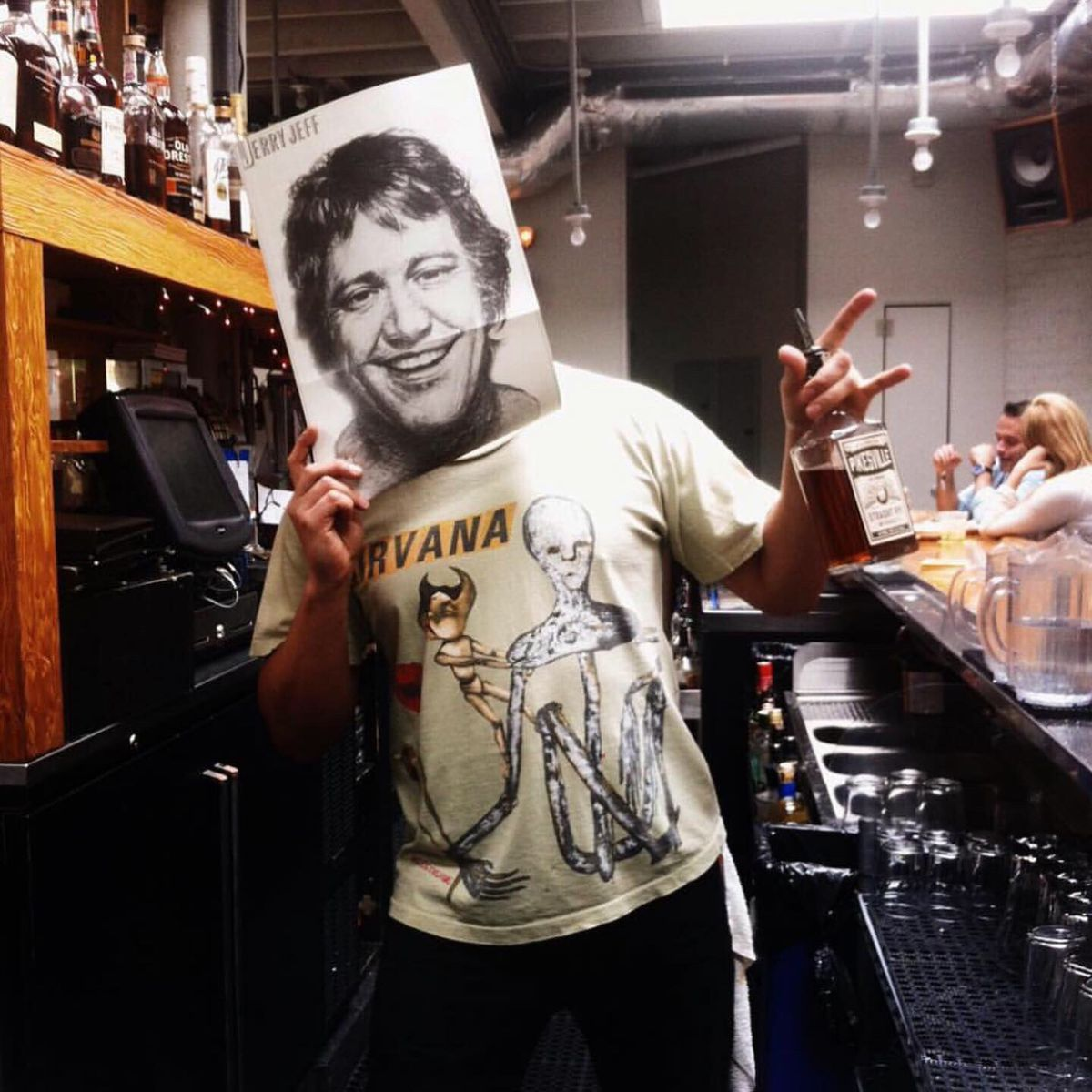 A former manager stands behind the bar holding a whiskey bottle in one hand and an album cover with a face on it in front of his own face in the other hand.