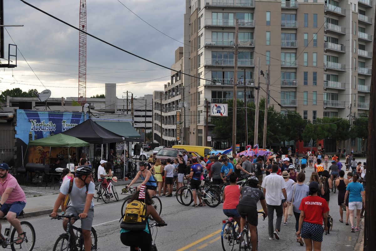 Pedestrians and cyclists jam the street, with a band performing on the sidewalk.