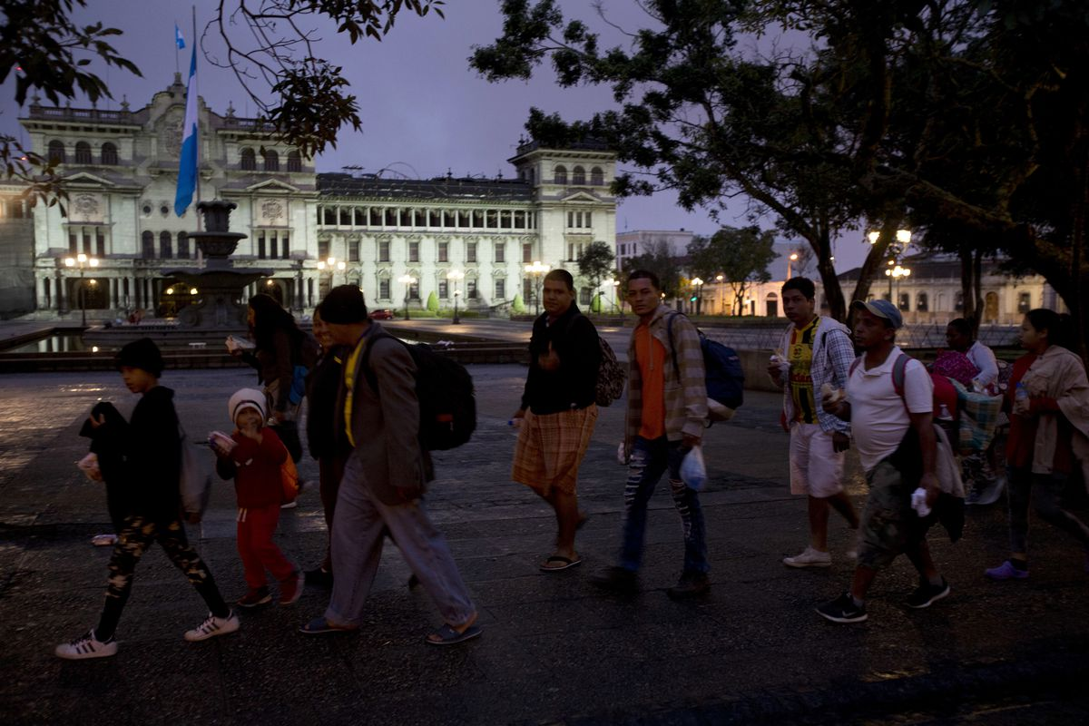 Honduran migrants walk past the National Palace as they leave Guatemala City at sunrise Thursday, Oct. 18, 2018 as they make continue their way north toward the U.S. Many of the more than 2,000 Hondurans in a migrant caravan trying to wend its way to the