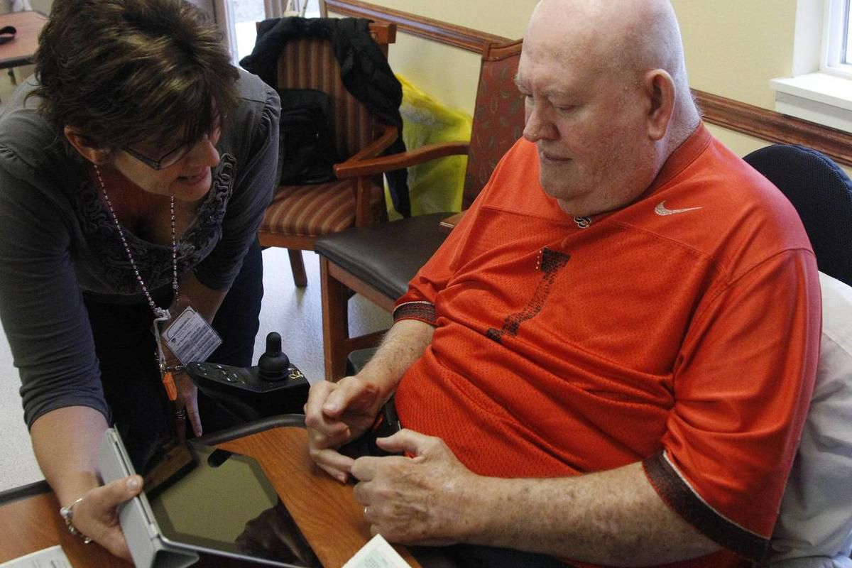 In this Friday, Nov. 4, 2011, photo, Lewis Crew, 75, receives help from a member of a voter assistance team while voting on a iPad, in Beaverton, Ore. Voters in five Oregonian counties are filling out and returning their mail-in ballots for a Tuesday, Nov
