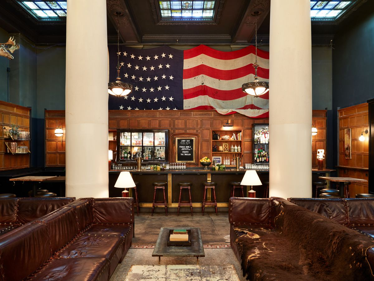 The lobby of the Ace Hotel features a large American flag hung over an antique wood bar, skylights, and leather sofas.