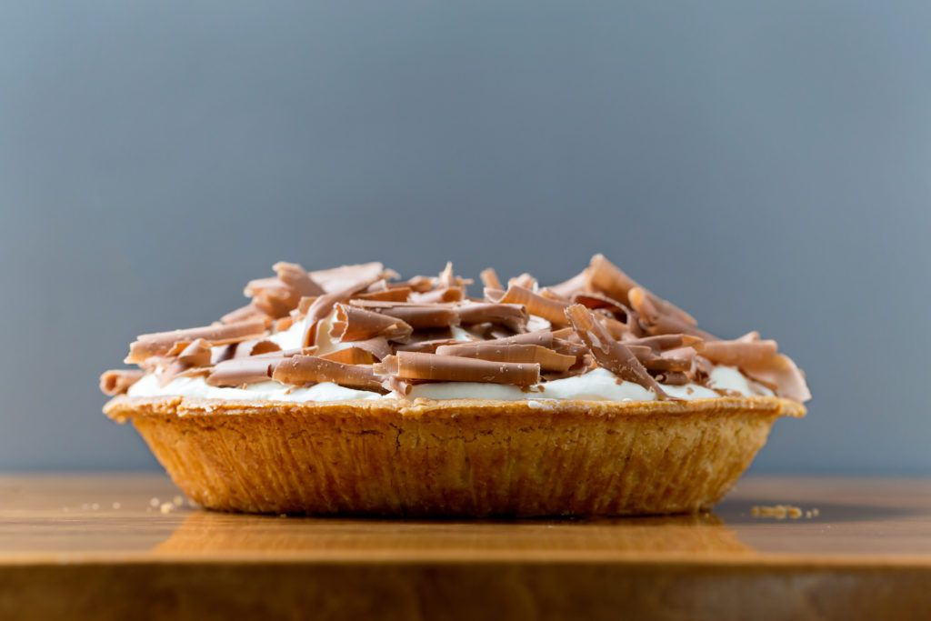 A pie topped with whipped cream and shaved chocolate