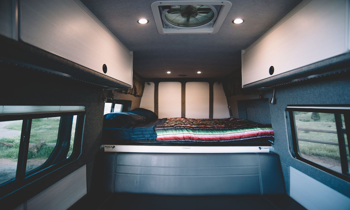 The interior of a camper van. There is a bed with patterned bed linens. There are storage cabinets along the top of the interior.