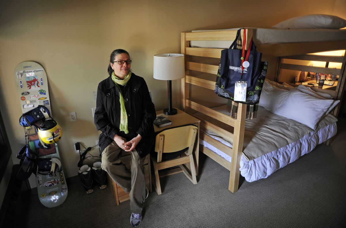 A woman sits on a small desk in her room, which also contains a snowboard and a bunk bed.