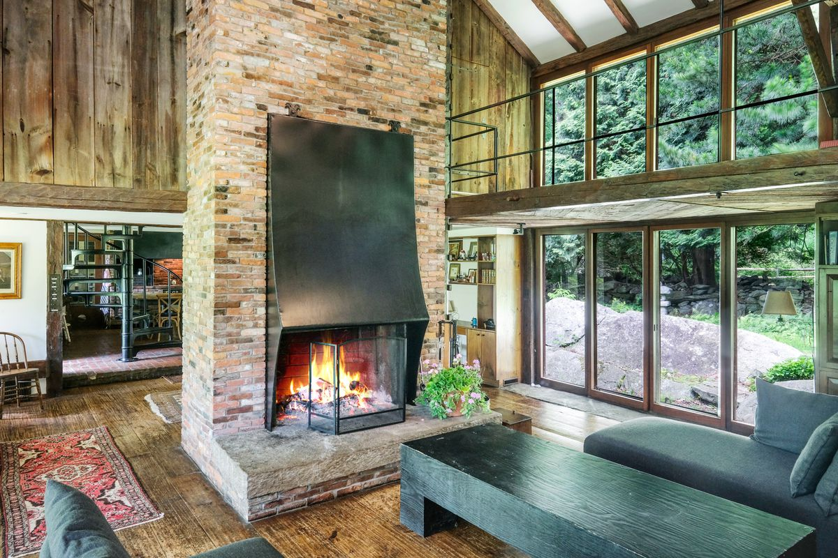 A brick fireplace sits in the middle of a large living room with vaulted ceilings. Windows and a second-story catwalk sit on the right side of the room.