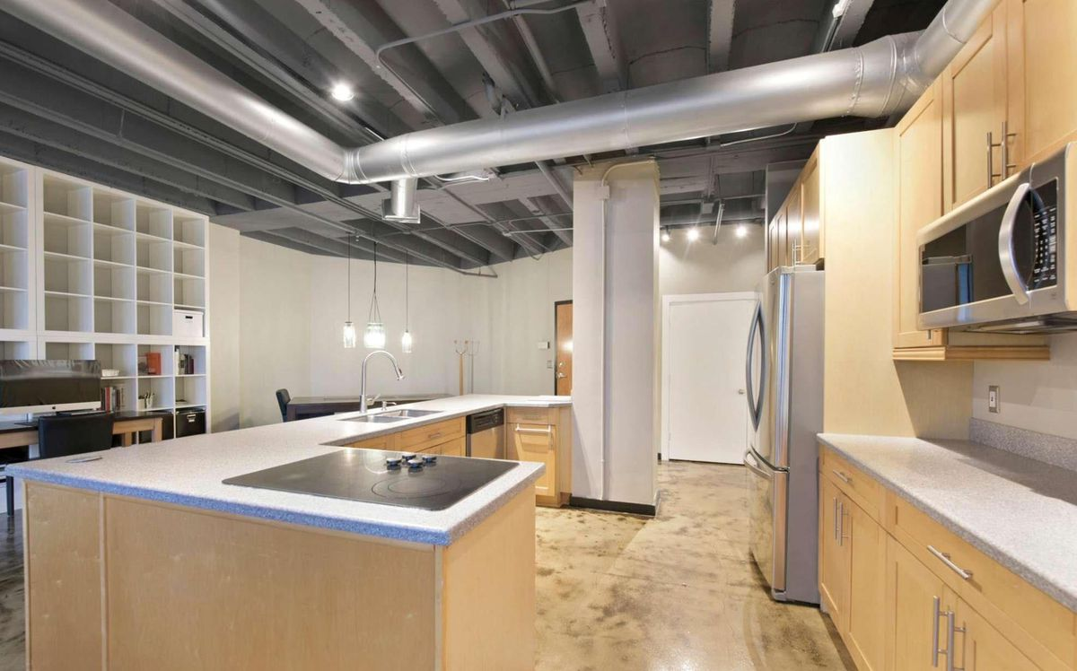 Loft kitchen with light wood oak cabinets, white countertops and stainless appliances.