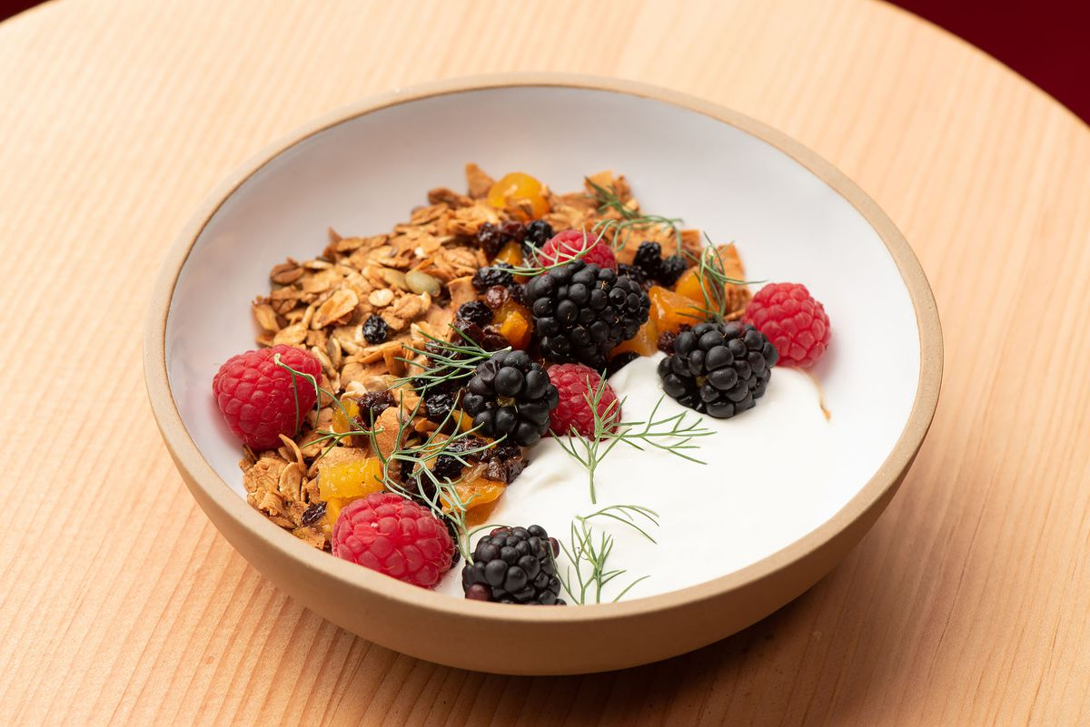 A big bowl of yogurt and granola on a wooden table.