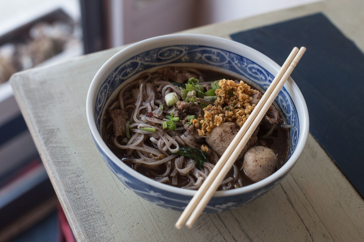 An ornate, blue-and-white bowl of noodles with chopsticks placed over it.