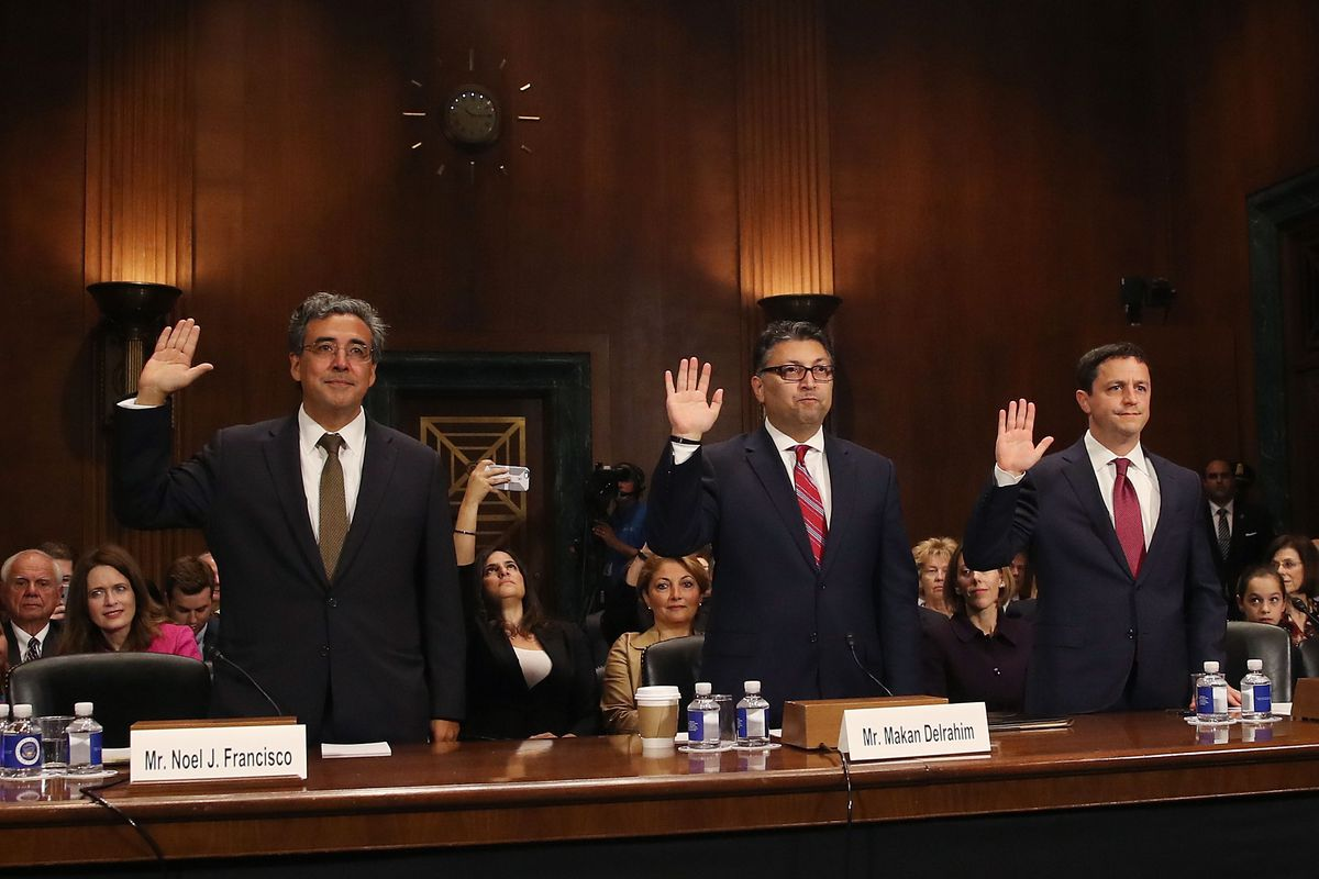 Three men stand behind a desk, each holding up his right hand to be sworn in during their Senate Judiciary Committee confirmation hearing.