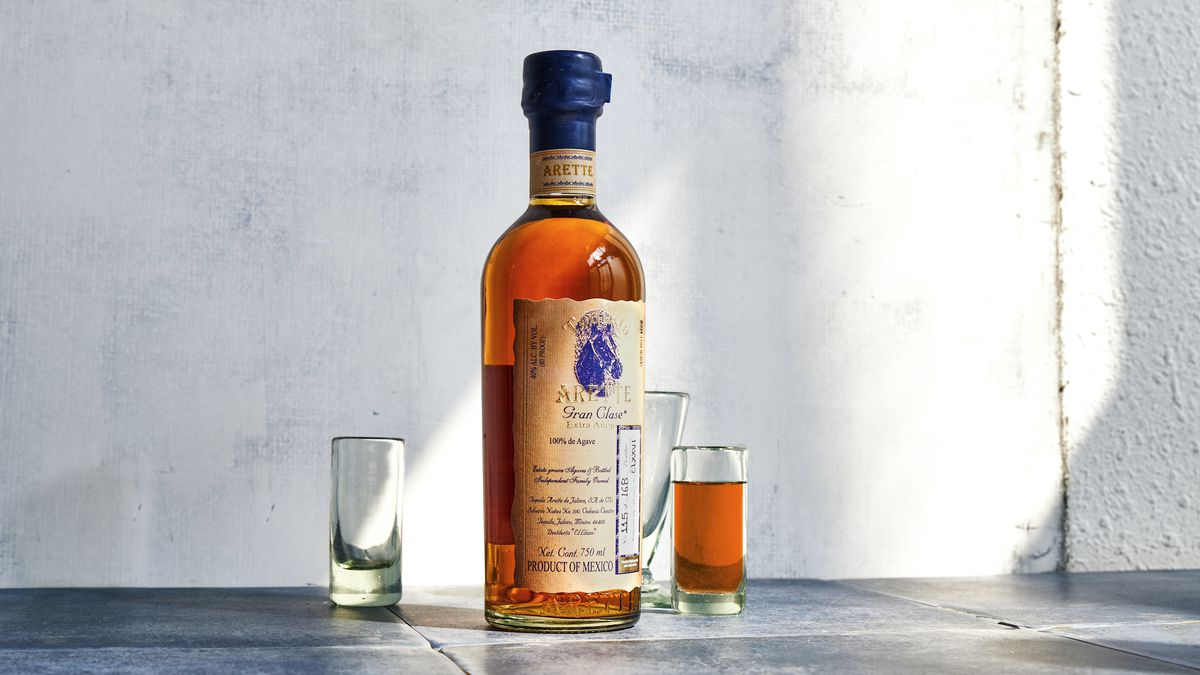 Amber-colored tequila in a bottle with a blue cap alongside a shot glass full of the tequila