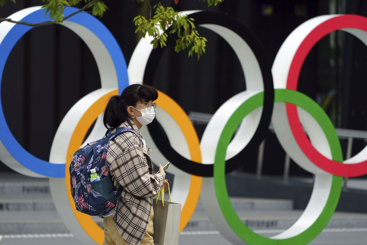 A woman wearing a protective mask to help curb the spread of the coronavirus walks in front of he Olympic Rings Tuesday, April 6, 2021, in Tokyo. The Japanese capital confirmed more than 390 new coronavirus cases on Tuesday.