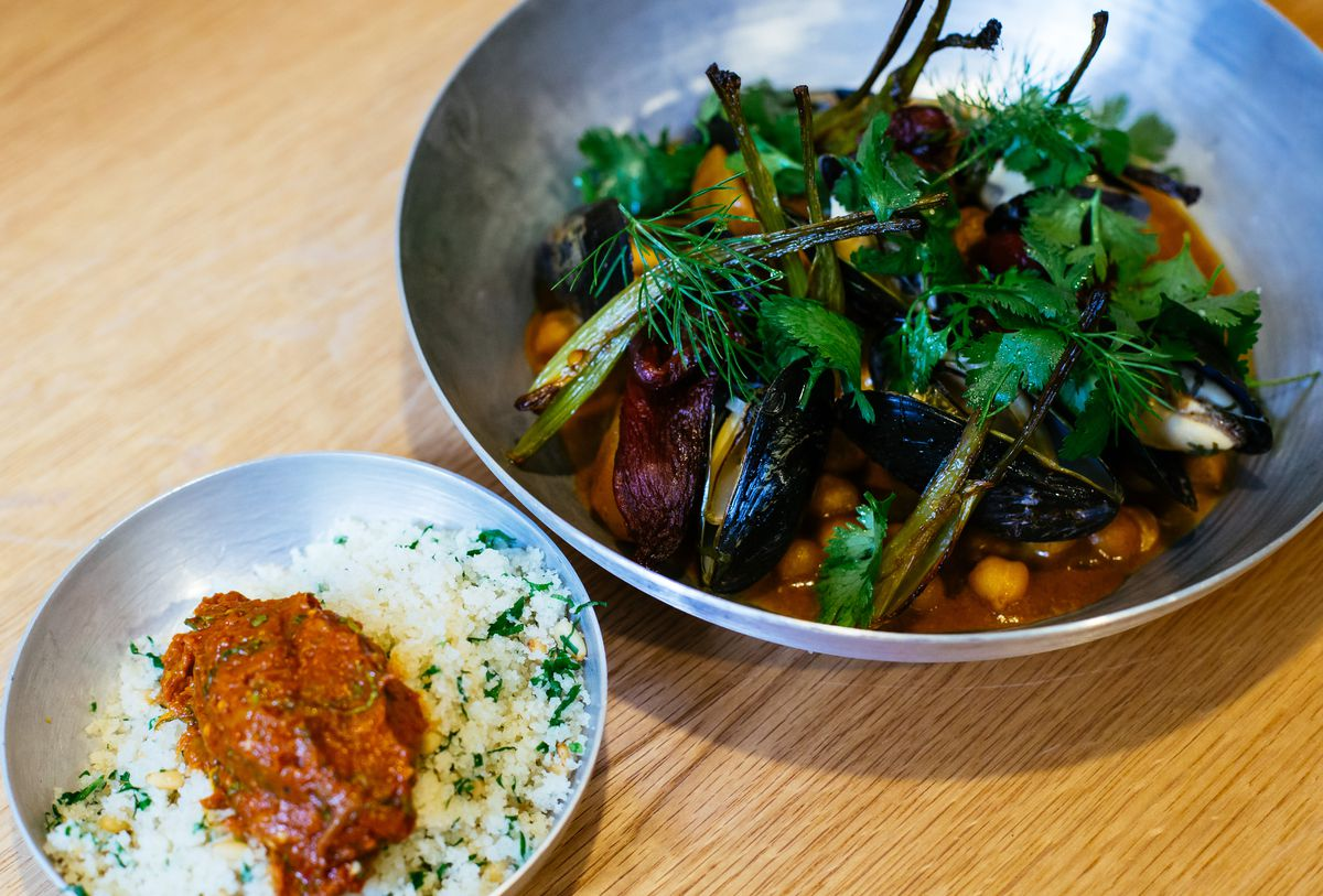 A stew with tomato, poached fish, and mussels, with a side of housemade couscous and pumpkin tershi