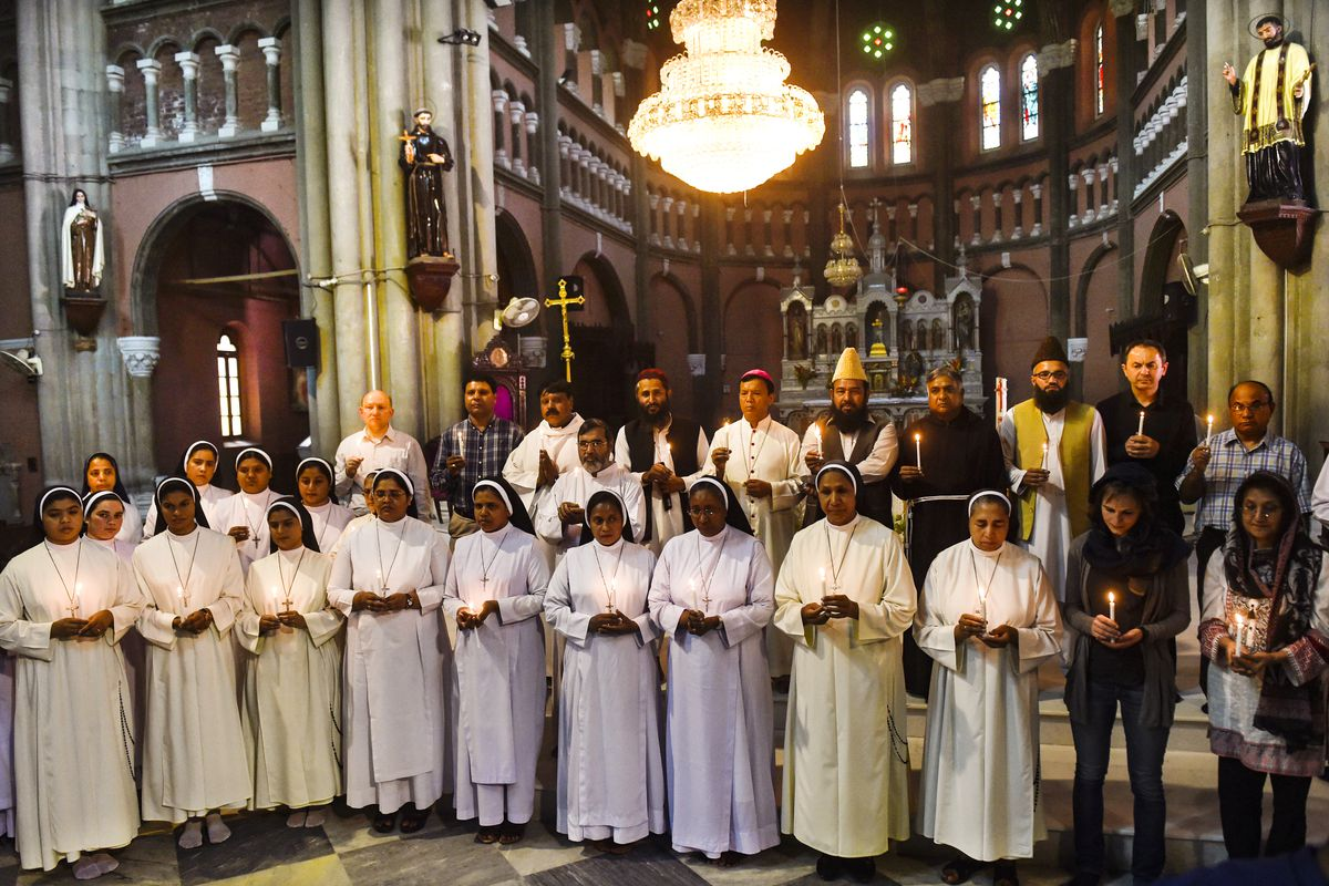 Pakistani Christians and Muslims hold candles at a tribute to Sri Lankan bomb blast victims at the Sacred Heart Cathedral Church in Lahore, Pakistan, on April 22, 2019.