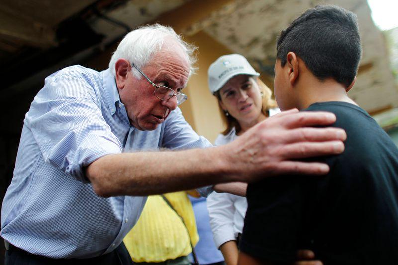 US Sen. Bernie Sanders (I- VT) talks to a child resident of the Playita community during a visit with the Mayor of San Juan, Carmen Yulin Cruz in San Juan, Puerto Rico, on October 27, 2017.