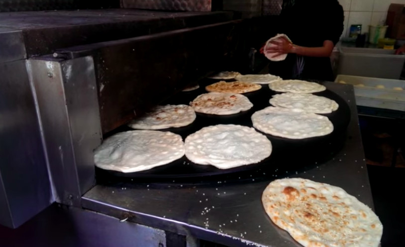 A grill covered in discs of uncooked flatbread dough, ready to go into an oven, with a baker in the background shaping one of the breads
