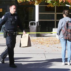 A police officer carries an evidence bag to his car at Mountain View High School in Orem after five students were stabbed in an apparent attack by a 16-year-old boy on Tuesday, Nov. 15, 2016.