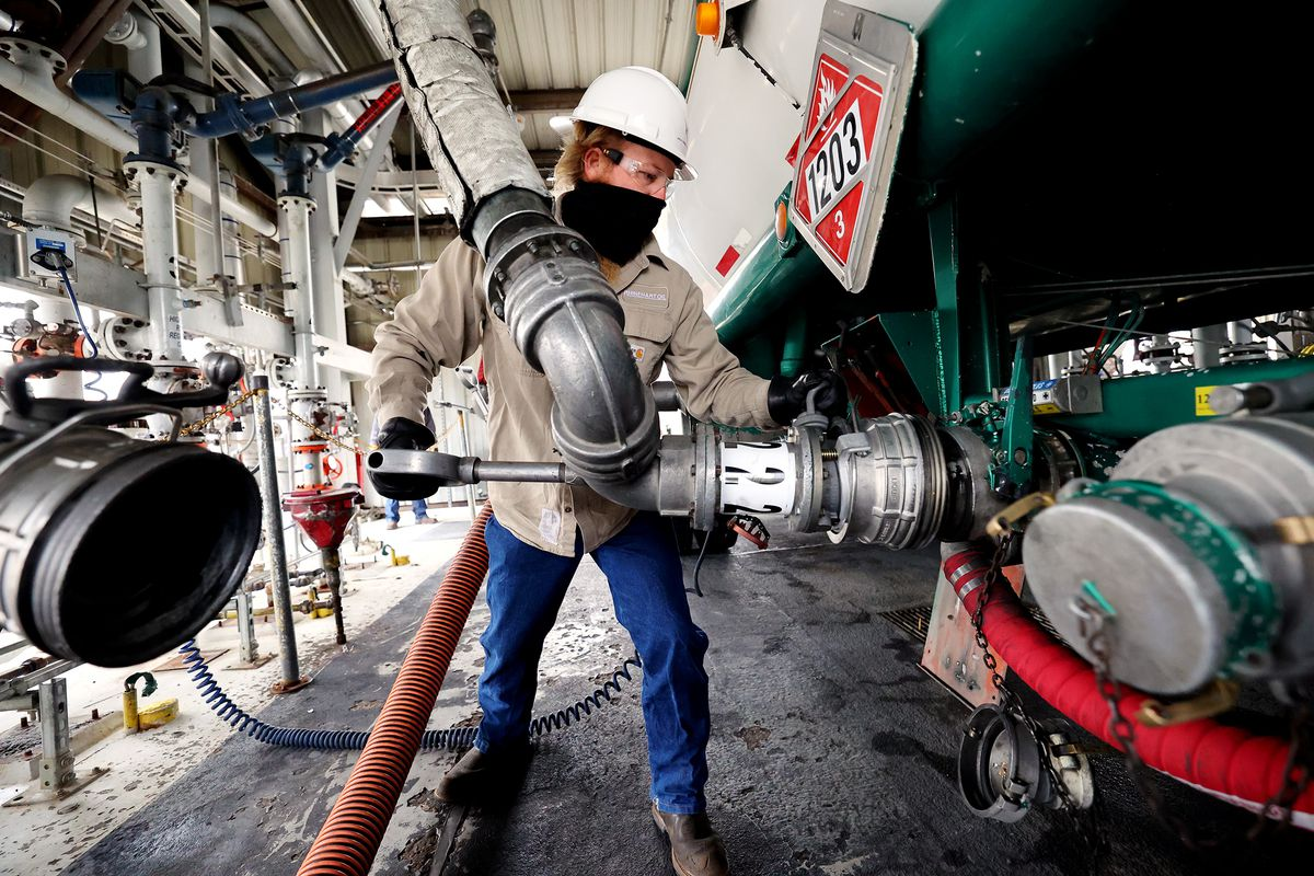 Fuel driver Matthew Perry, of Rhinehart Oil, connects a pump line to an 8,000 gallon transport trailer as he prepares to fill it with Tier 3 fuel at the HollyFrontier refinery in Woods Cross on Friday, Dec. 11, 2020. Earlier, Gov. Gary Herbert, Mike Jennings, HollyFrontier president and CEO, and Scott White, vice presidentand refinery manager, held a ribbon-cutting ceremony to celebrate the completion of the refinery's effort to bring cleaner burning Tier 3 fuels to market along the Wasatch Front.