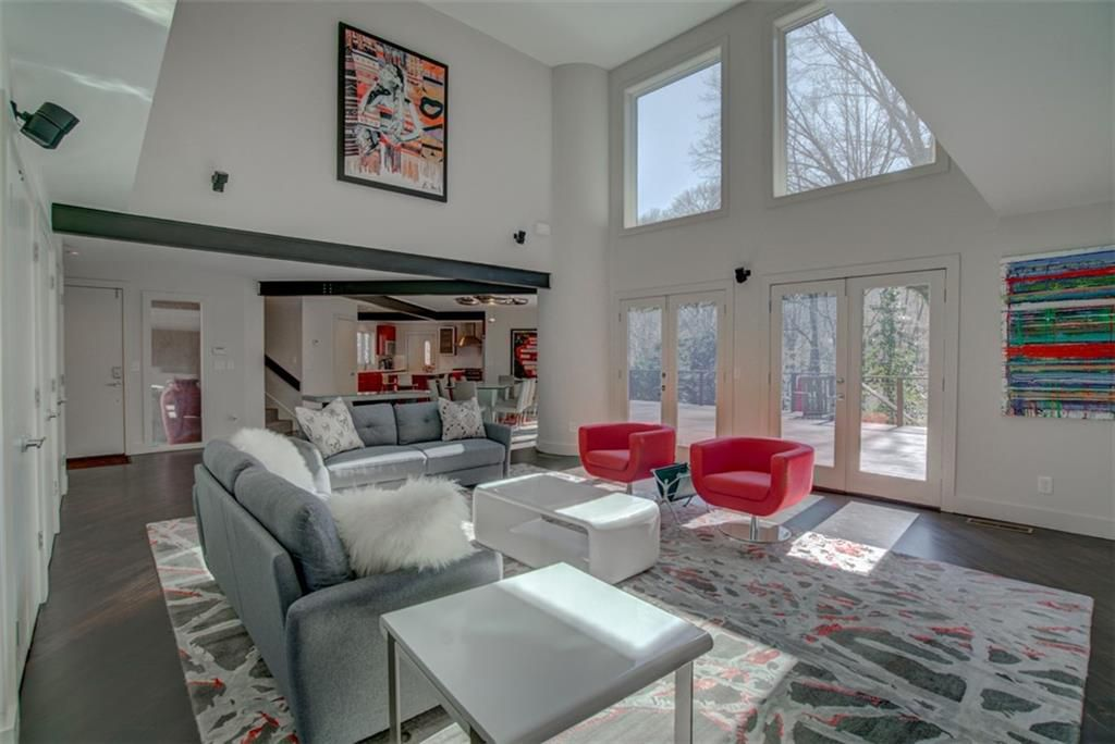 A huge white living room with two stories of windows and red chairs.